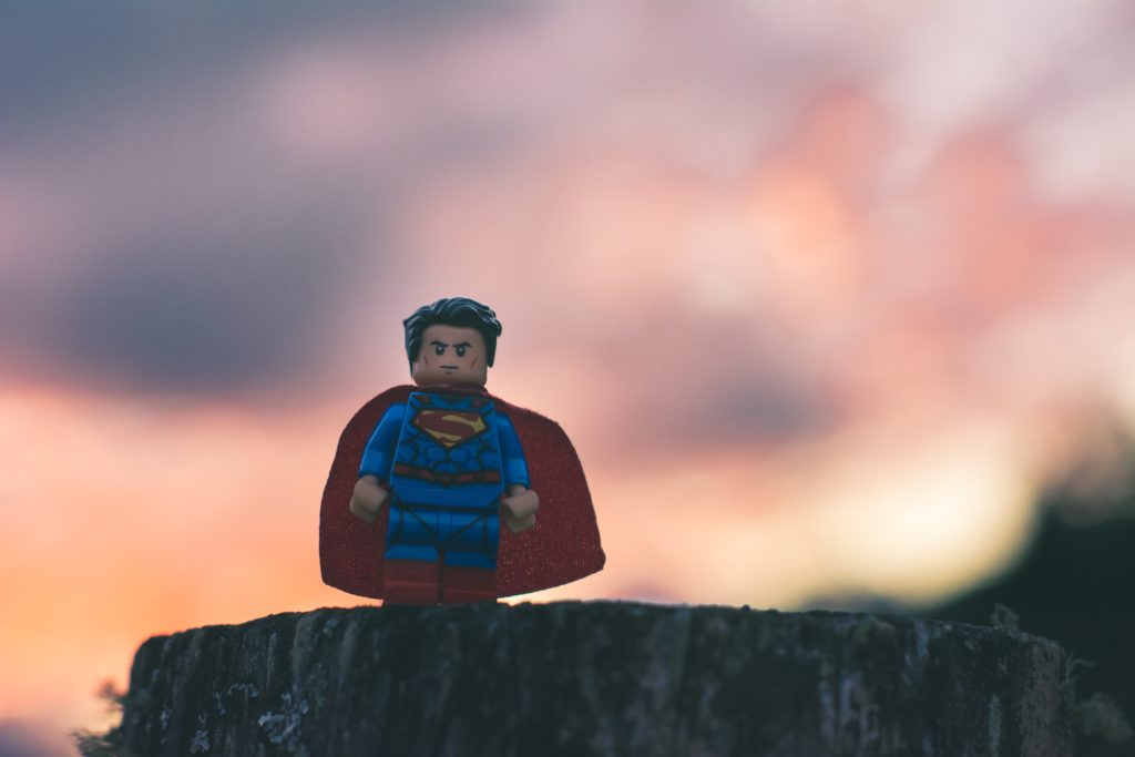 A Lego super-hero with a stern face stands atop a rock mountain. There are storm clouds around him.